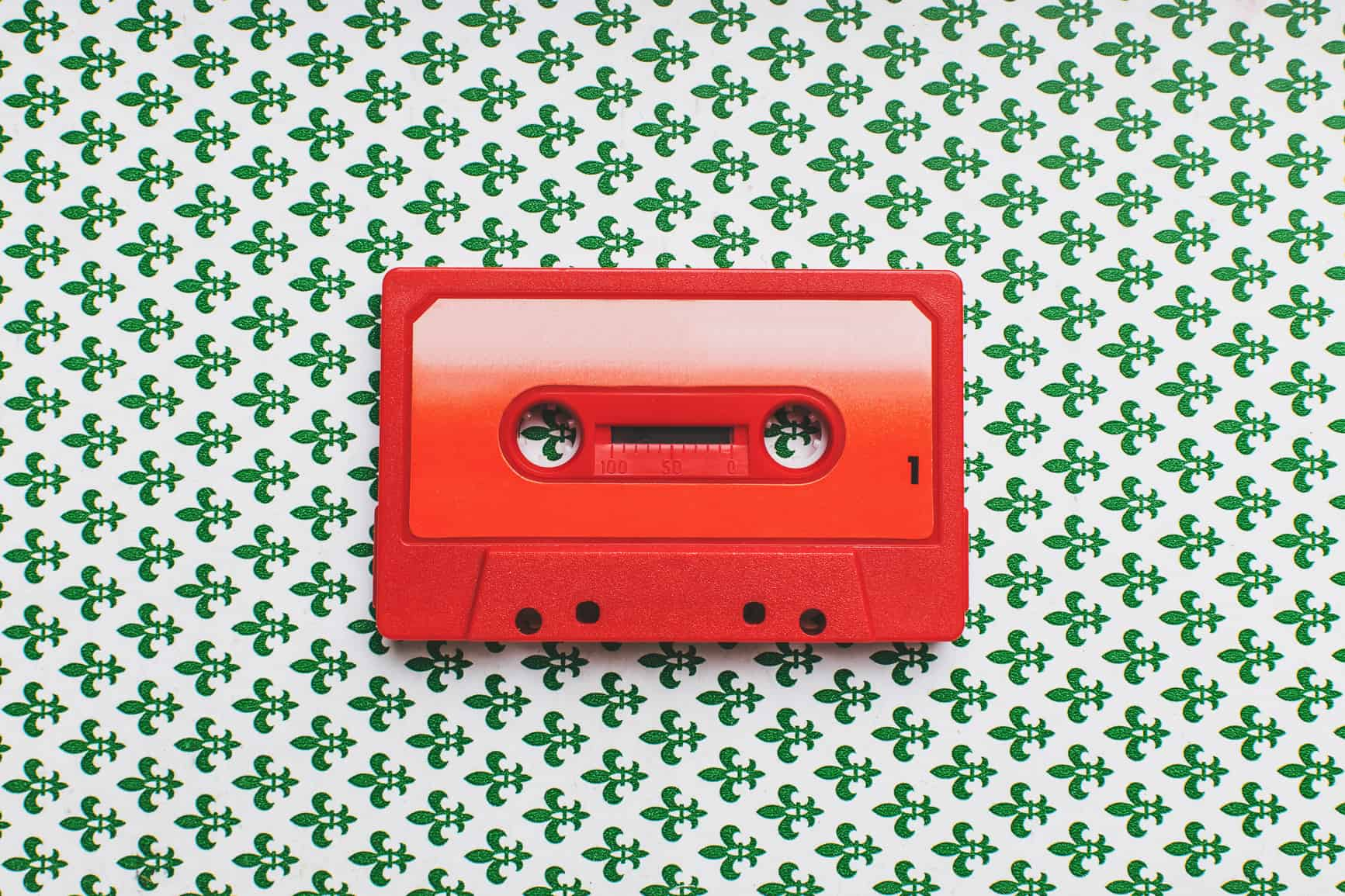 Red cassette tape on green background