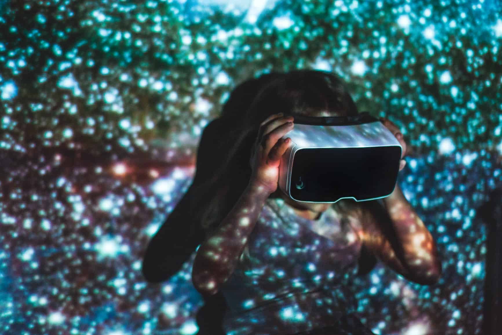 Girl using virtual reality headset surrounded by colours
